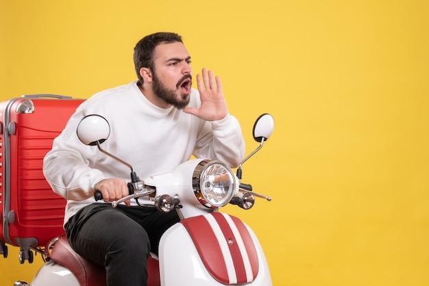 スーツケースを乗せたバイクに座って、孤立した黄色の背景に驚いた表情で誰かを呼び出す若い男のトップビュー