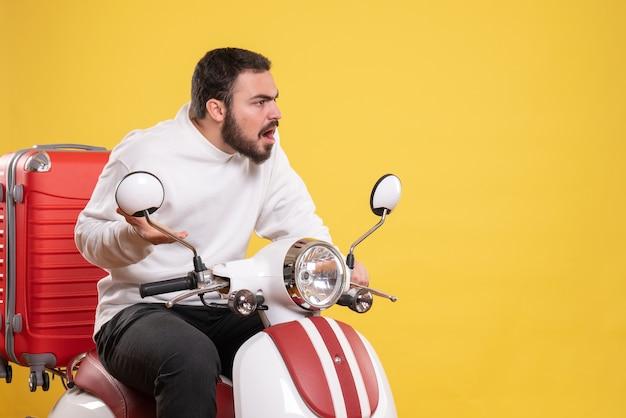 スーツケースを乗せたバイクに座って、孤立した黄色の背景に驚いた表情で何かを見ている若い男のトップビュー