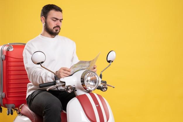 孤立した黄色の背景に地図を見て、スーツケースを持ってオートバイに座っている若い男のトップ ビュー