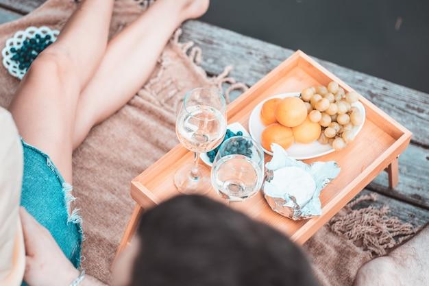 강이나 호수 근처 피크닉에서 알아볼 수 없는 젊고 행복한 커플, 야외에서 함께 와인을 마시는 여성, 남성, 여름 휴가를 즐기는 사람들, 사랑의 감정