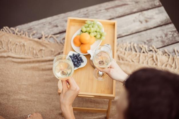 강이나 호수 근처 피크닉에서 알아볼 수 없는 젊고 행복한 커플, 야외에서 함께 와인을 마시는 여성과 남성, 휴가를 즐기는 사람들, 감정을 사랑하는 사람들의 상위 뷰