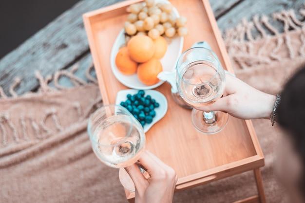 강이나 호수 근처에서 낭만적인 피크닉을 하며 알아볼 수 없는 젊고 행복한 커플, 야외에서 함께 와인을 마시는 여성, 남성, 휴가를 즐기는 사람들, 사랑의 감정