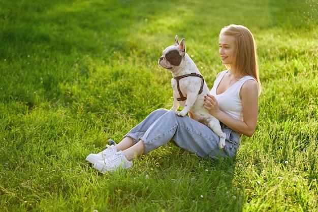 사랑스러운 프랑스 불독 잔디에 앉아 젊은 행복 한 여자의 상위 뷰. 화려한 백인 웃는 소녀 여름 석양을 즐기고, 도시 공원에서 무릎에 개를 들고. 인간과 동물의 우정.