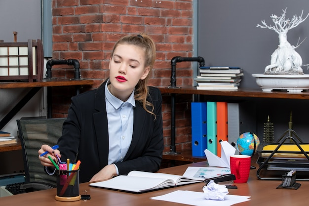 テーブルに座って、オフィスでペンケースにペンを配置する若い女性の上面図