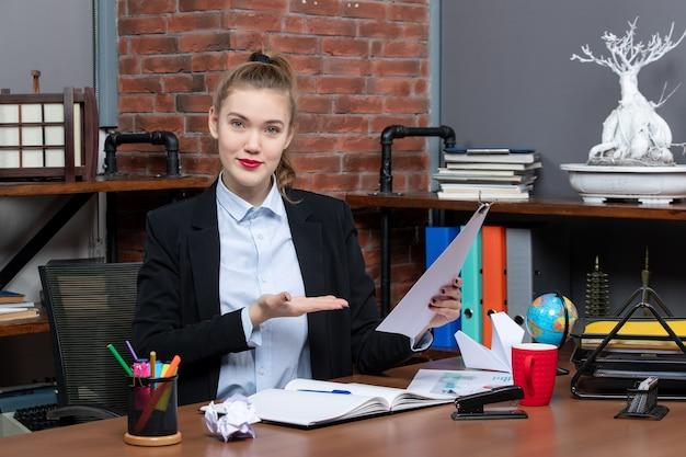 テーブルに座って、オフィスでドキュメントを表示して保持している若い女性の上面図