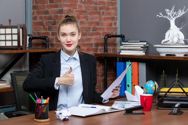 Вид сверху молодой леди, сидящей за столом и держащей документ, делая жест в офисе
