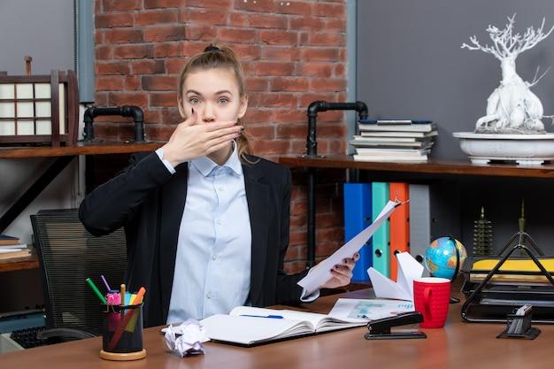 テーブルに座って、オフィスであくびをしているドキュメントを保持している若い女性の上面図