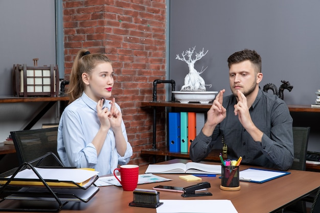 オフィス環境で夢を見ている若い男性と彼の女性の同僚の上面図
