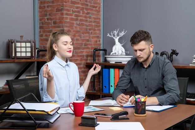 그의 여성 동료가 사무실 환경에서 꿈꾸는 동안 한 문제에 집중하는 젊은 남자의 상위 뷰