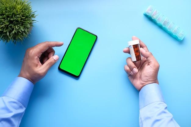 Вид сверху руки молодого человека, использующего смартфон и держащего контейнер для таблеток