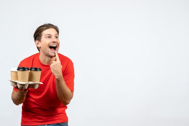白い背景の上の笑顔のジェスチャーをする注文を保持している赤いブラウスの若い男の上面図