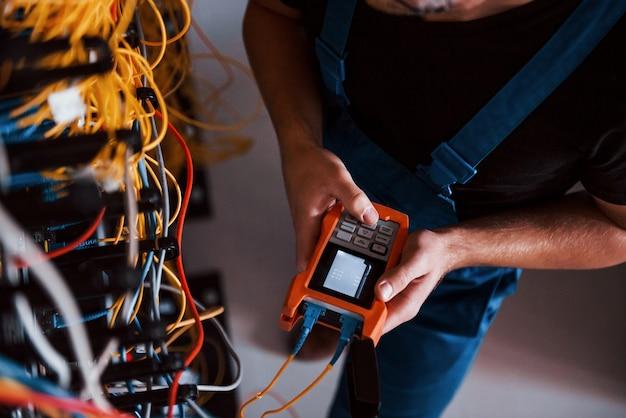 Вид сверху молодого человека в форме с измерительным прибором, который работает с интернет-оборудованием и проводами в серверной.