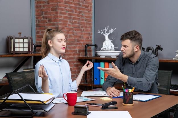 若い男の上面図は、オフィス環境で彼の女性の同僚に腹を立てています