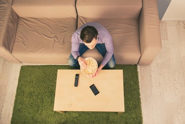 Вид сверху на молодого человека, отдыхающего дома, смотрящего фильм и едящего попкорн