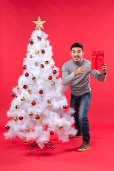 飾られた白い新年の木の近くに立って、彼の贈り物を保持している若い男の上面図