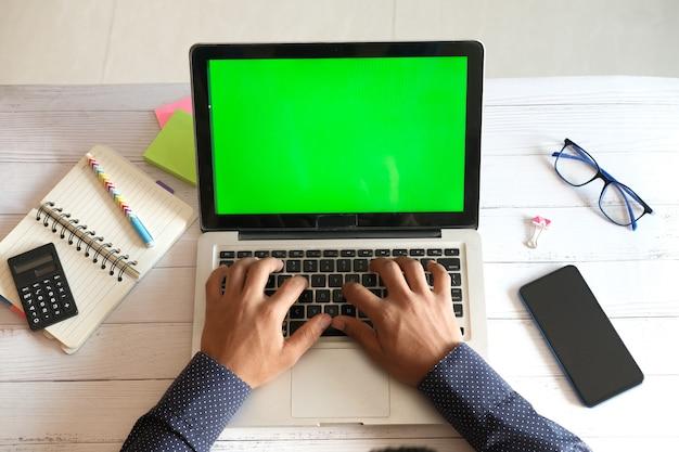 オフィスの机の上の空白の画面でラップトップを使用して若い男の上面図