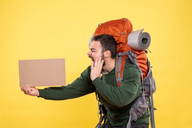 Вид сверху на молодого нервного эмоционального путешествующего парня с рюкзаком, держащего лист без надписи на желтом