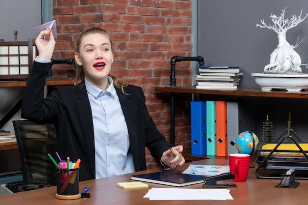 책상에 앉아 종이비행기를 하는 젊은 긍정적인 여성 회사원의 상위 뷰