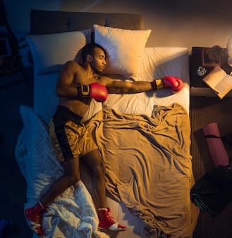 若いプロのボクサー、手袋をはめてスポーツウェアで彼の寝室で寝ている戦闘機の上面図