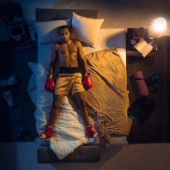 Вид сверху молодого профессионального боксера, борца, спящего в своей спальне в спортивной одежде с перчатками