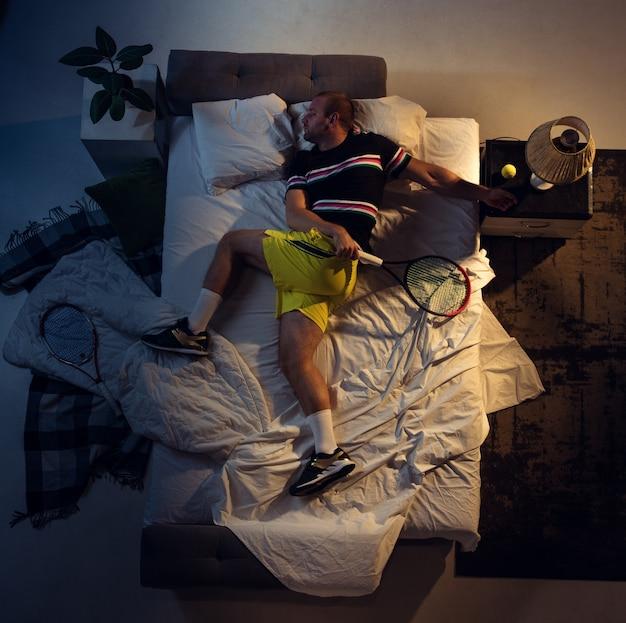 Вид сверху на молодого профессионального теннисиста, спящего в своей спальне в спортивной одежде с ракеткой
