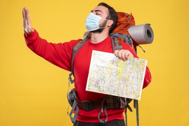 Вид сверху на молодого гордого парня-путешественника в медицинской маске с рюкзаком, держащего карту на желтом