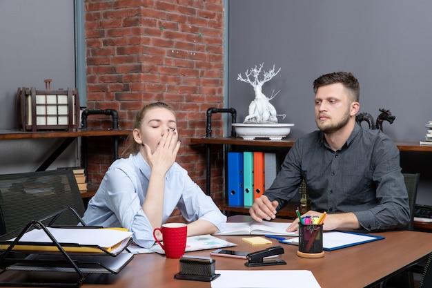 若い眠そうな女性労働者とオフィス環境のテーブルに座っている彼女の男性の同僚の上面図