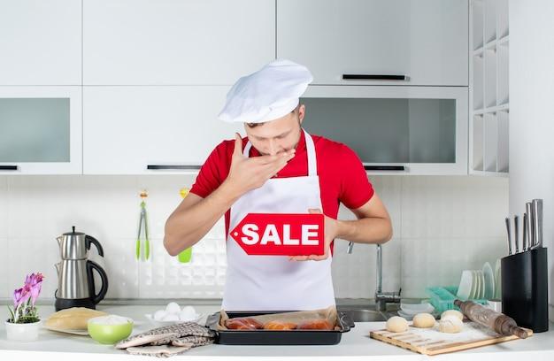 白いキッチンで販売サインを示す若い眠そうな男性シェフのトップ ビュー