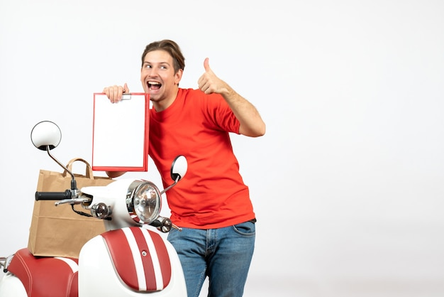 白い壁にokジェスチャーを作るドキュメントを示すスクーターの近くに立っている赤い制服を着た若い笑顔の配達人の上面図