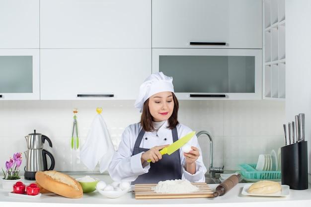 白いキッチンで卵とナイフを保持しているテーブルの後ろに立っている制服を着た若い笑顔の女性シェフの上面図