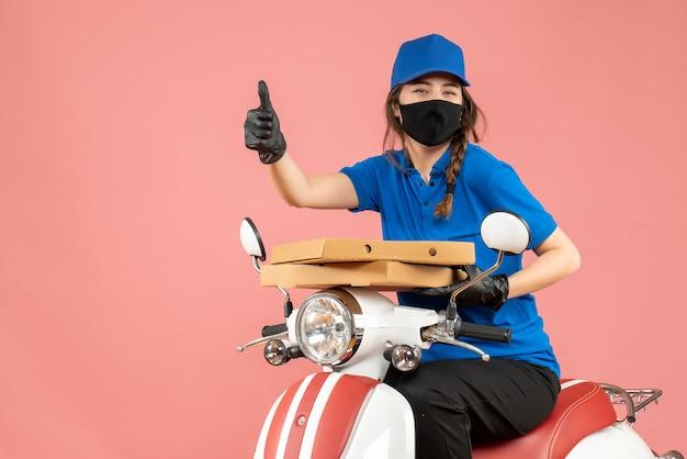 医療用マスクとスクーターに座っている手袋を身に着けている若い笑顔の女性宅配便のトップ ビュー