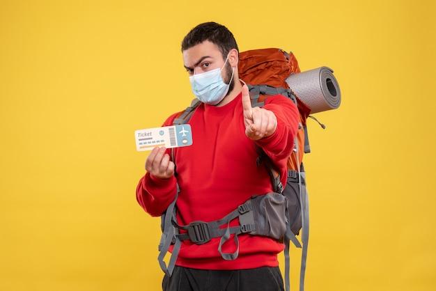 노란색에 하나를 보여주는 티켓을 들고 배낭과 의료 마스크를 착용하는 젊은 여행자 남자의 상위 뷰