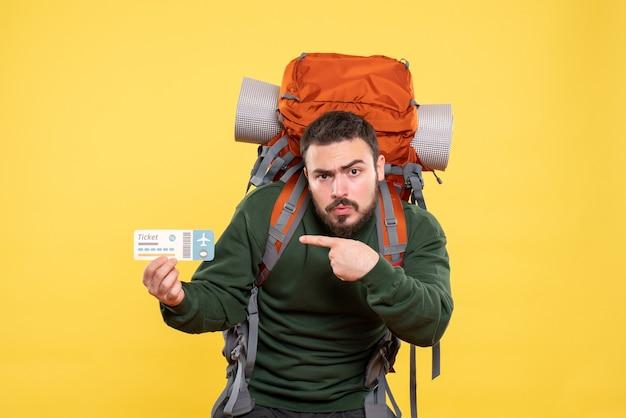 Вид сверху молодого путешествующего парня с рюкзаком и показывающего, что билет смущен на желтом