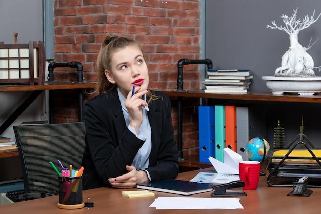 그녀의 책상에 앉아 카메라를 위해 포즈를 취하는 불확실한 불확실한 젊은 여성 회사원의 상위 뷰