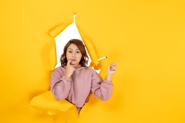 Вид сверху молодой женщины смущенной указывая что-то и свободное пространство на желтом разорванном