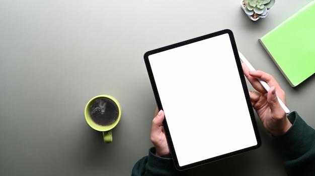 Взгляд сверху молодой женщины в зеленом свитере держа перо стилуса и цифровую таблетку с пустым экраном на серой таблице.