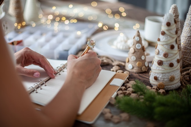 젊은 여자의 상위 뷰는 손수 크리스마스 트리 장식, 별, 단추 및 마시맬로 차가있는 책상에 일기에 2021 년 새해 목표를 쓰고 있습니다. 새로운 목표를 계획하는 개념.