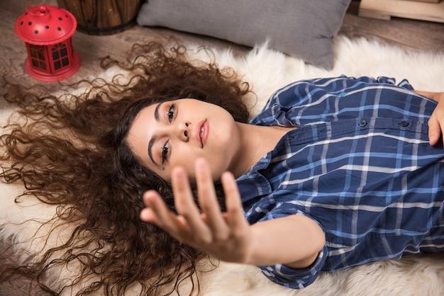 카펫에 누워 있는 젊은 여성의 상위 뷰