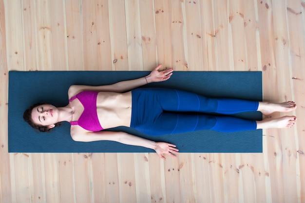 Взгляд сверху молодой женщины лежа в трупе или представлении трупа ослабляя после практики йоги