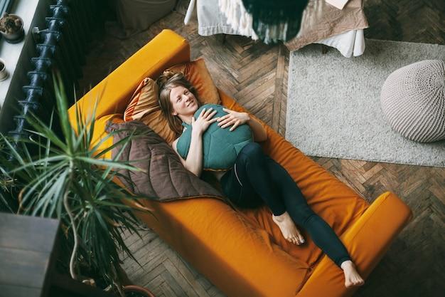 自宅のソファに横たわっている若い女性の上面図