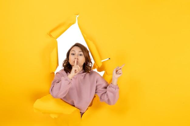 何かを指している沈黙のジェスチャーをしている若い女性の上面図と黄色の引き裂かれた空きスペース