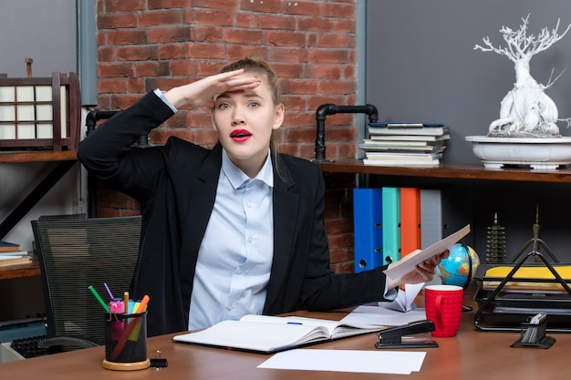 テーブルに座って、オフィスで何かを注意深く見ているドキュメントを保持している若い女性の上面図