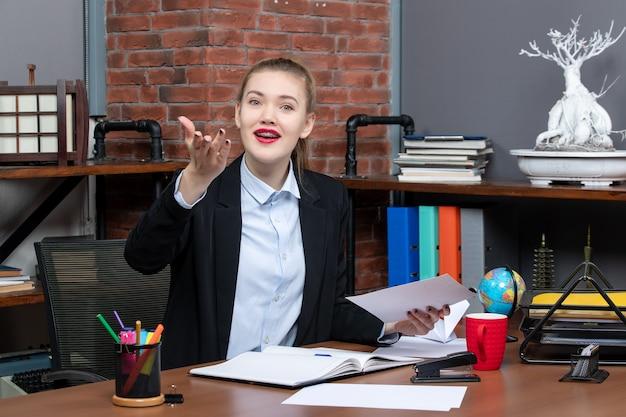 テーブルに座って、オフィスで笑顔のフェイシア表現で何かを注意深く見ているドキュメントを保持している若い女性の上面図