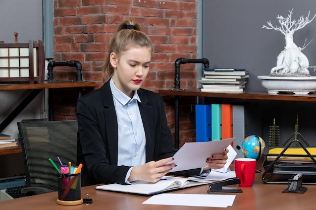 テーブルに座って、オフィスで何かを注意深く読んで文書を保持している若い女性の上面図