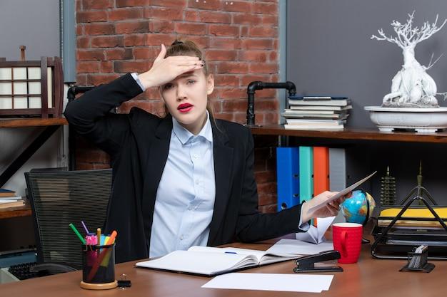 テーブルに座って、オフィスで頭痛に苦しんでいるドキュメントを保持している若い女性の上面図 無料写真