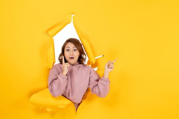 찢어진 노란색에 뭔가와 여유 공간을 가리키는 생각하는 젊은 여자의 상위 뷰