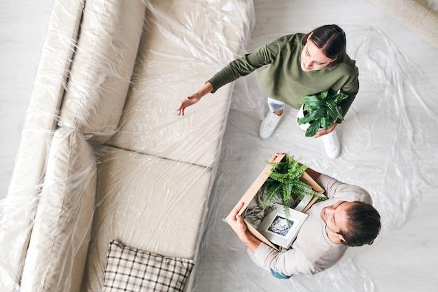 両方がソファで床に立っている間、彼女の夫と話している緑の国内植物を持つ若い女性の上面図