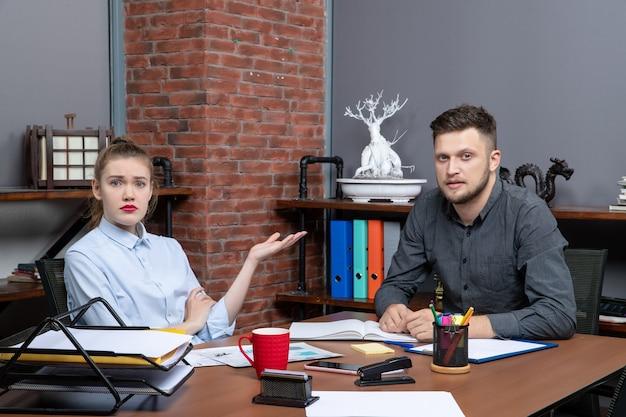 Вид сверху молодой удивительной офисной команды, сидящей за столом, обсуждающей один важный вопрос в офисе