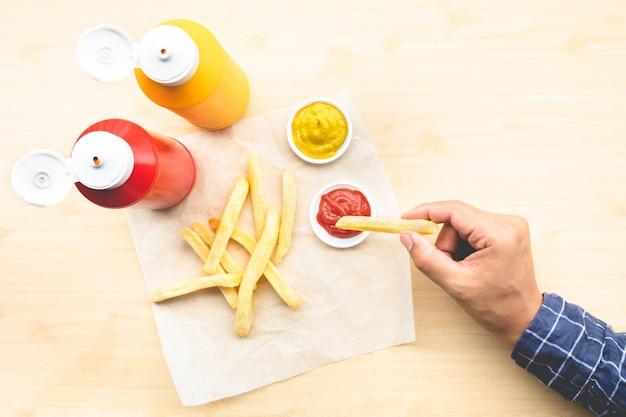 젊은이의 상위 뷰는 프랑스 튀김과 디핑 소스로 식사를 즐깁니다.