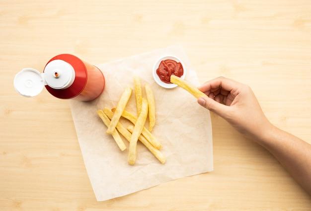 Вид сверху молодой женщины, окунающей французский жареный с томатным соусом (кетчупом) на фоне деревянного стола. идеи быстрого питания и здоровых концепций